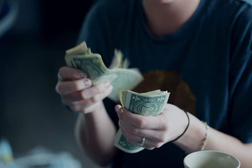 Woman counting a stack of one dollar bills.