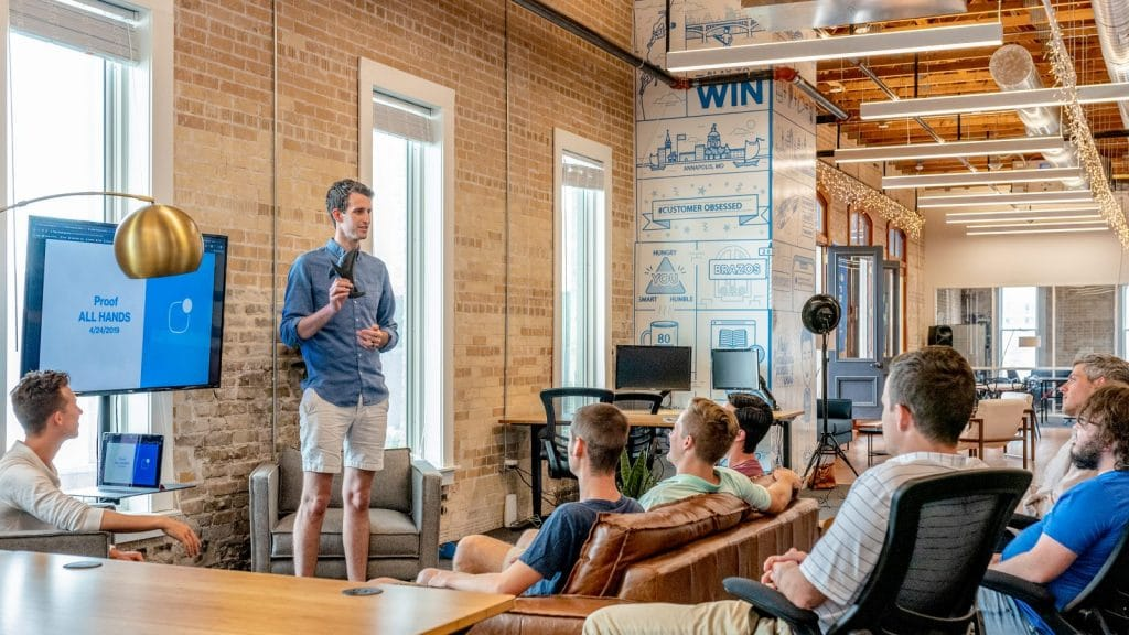 "Man in casual clothing giving a presentation to seated employees in a ""startup"" environment."
